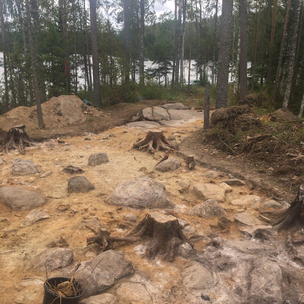 Kuvassa osa kaivausaluetta, hiekkaa ja kiveä, taustalla järvi ja metsää.